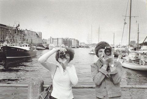 Her oser det 1970-tallet. Det kan en kanskje se ut fra hårfrisyrer og ikke minst kameraene som brukes. De store tunge speilreflekskameraene er i våre dager stort blitt historie blant turister. Dagens turister på Torget klarer seg med gode smarttelefoner og selfiestenger. Foto: MORGENAVISENS ARKIV