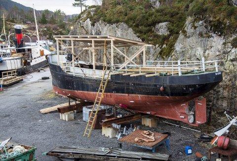Slik står den gamle brannbåten i dag - på land hos Dåfjorden Slipp på Stord. Bildet er tatt i nyttårshelgen, og viser overbygget som er klart. Nå skal det snart lages overbygg som dekker resten av båten. Foto: EIRIK HAGESÆTER