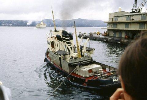 Vi vet ikke hvem som har tatt dette bildet, men det kan være en turist om bord i et cruiseskip. Ute på Byfjorden ser vi en av Bergenskes Englandsbåter, mens Vulcanus hjelper et cruiseskip ut fra kai. Om bord Vulcanus er begge livbåtene hengende i daviter, og begge luftelurene er godt synlig ved siden av skorsteinen med BDS-ringene.