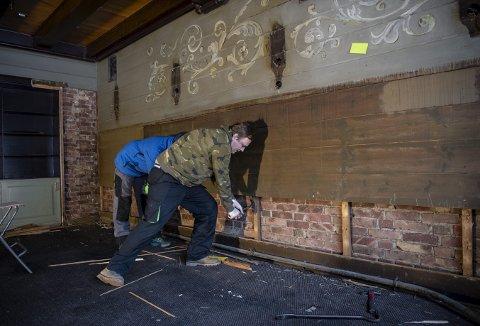Her er Tom Rune Olsen og Alexandru Silviu Buzatu i full gang med å demontere panelet på veggene. Og det skjer med stor forsiktighet. – Alt kan brukes etterpå, mener Roger Iversen. Foto: RUNE JOHANSEN