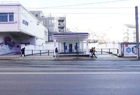 Inneklemt, og for anledningen lilla farget som følge av megaskjermen hos Media City på motsatt side av Lars Hilles gate, ligger den lille veteranstasjonen og venter på det endelige fredningsvedtaket. Foto: TOM R. HJERTHOLM