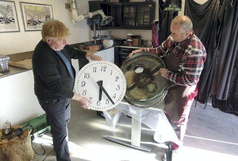Arvid Holum (t.v.) og Magne Waagenes hos Bygg og Ventilasjon på Nøstet tar en kikk på klokken. De to mestrene ser på det å restaurere den gamle klokken som en del av å ta vare på byens identitet. Foto: TOM R. HJERTHOLM