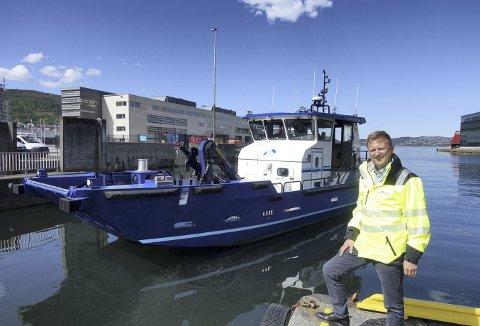 Havnedirektør Johnny Breivik med den flunkende, MB Sydnes i bakgrunnen. Når båten glir fra kai her i indre havn, skjer det fullstendig lydløst som følge av at den da er batteridrevet. Foto: TOM R. HJERTHOLM