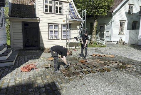 Snekker Leander Riple Vetti (t.v.) og tømrer Svein Erik Bjordal gjør ren alle de gamle pannesteinene, før de skal tilbake på Glassmesterhuset. Selve taket har og fått et nødvendig løft. Det er i år nøyaktig 60 år siden Glassmesterhuset ble revet og senere kom til Gamle Bergen Museum. Foto: TOM R. HJERTHOLM