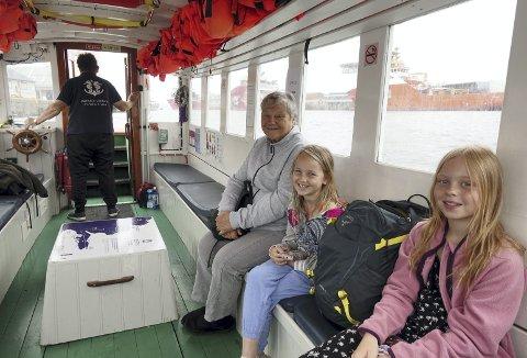 Skipper på BEF 1, Kjell Kolstad ved roret, mens farmor Elin-Wenche Pedersen og søstrene Edel (8) og Inez (10) koser seg med hele fergen for seg selv på denne turen fra Rundetårn til Gamle Bergen Museum i Elsesro. Foto: TOM R. HJERTHOLM