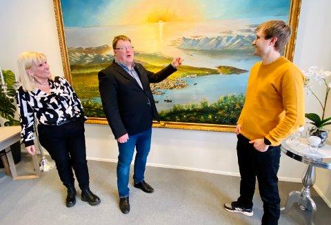 Ordfører Kari-Anne Opsal, kommunedirektør Hugo Thode Hansen og Anders Remme Olsen i Tian Gruppen er alle fornøyde med at kulturskoletilbudet på Grøtavær er sikret. Her står de foran et maleri som har utsikt nettopp den veien.