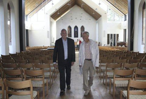 GLEDER SEG: Sokneprest Espen Feilberg Jacobsen (til venstre) og leder av byggekomiteen Frank Hagen smiler forventningsfulle der de går nedover midtgangen i den nye kirken. Alle de 500 stolene er nå på plass, og blyglassmaleriene er gjenkjennelige på den bakerste kirkeveggen. Foto: Aina Moberg