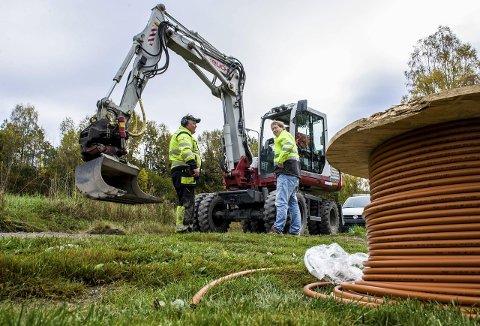 500 om dagen: Per Arne Holt (t.v.) og Tom Hvaal (i gravemaskinen) graver ned rundt 500 meter rør om dagen, konstaterer André Lunde fra Viken Fiber. Foto: Bjørn Jakobsen