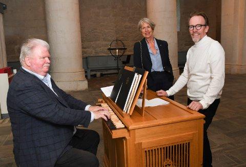 Venter fortsatt: Det nye orgelet i Ringsaker kirke er ikke på plass før sommeren 2024. Imens må Roger Andreassen gi menigheten vakre toner på kirkens midlertidige orgel. Foran ser vi Lise Holland og Kai Ove Berg.