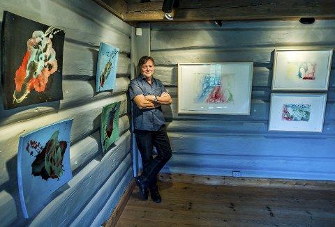70 KUNSTVERK: Ole Dørje midt blant noen av dronning Sonjas bilder. Hun har med hele 70 kunstverk på utstillingen.