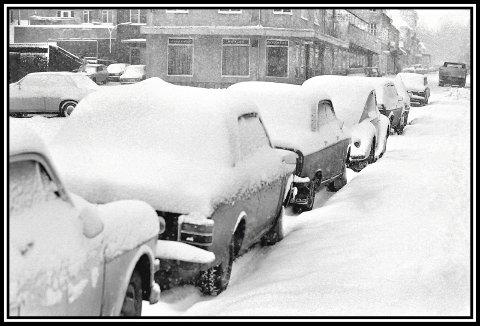 1977.: Mye snø og vinter dette året. Folk med jobb i sentrum parkerte her, i Jernbanegata også, gratis. Og de som bodde i sentrum, parkerte også i gatene ofte. Det var jo ikke så mange leilighetskomplekser da, med påkrevde parkeringshus under bakken. Spesielt her er jo solide Sparebankgården, ferdig i 1957/58, der er vel den første parkeringen under bakkeplan i Sarpsborg. Snøen var hvit og fin den gangen, men fortauene ser litt nedsnødde ut her. Sikkert fordi det bøttet ned med snø da bildet ble tatt. Litt lenger opp i gata ligger jo Ny Form Finn Sørlie sin legendariske møbelforretning. Til høyre ligger vel gode gamle Lyn Elektro. Til venstre på bildet sees nedkjøringen til lageret som Finn Sørlie bygde noen år før dette bildet ble tatt. Det er i dag også parkeringskjeller for blokka til venstre i Oscarsgate.