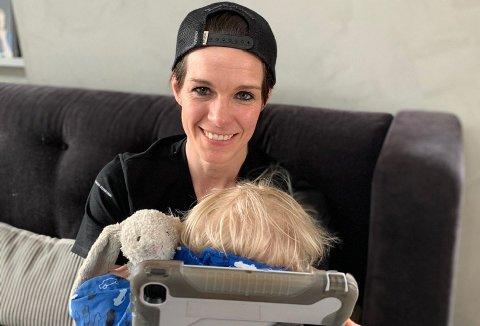 HJEMMEKONTOR: Anja Hammerseng-Edin med minste mann på fanget og samtidig som hun har hjemmeundervisning for eldstemann. Foto:Privat