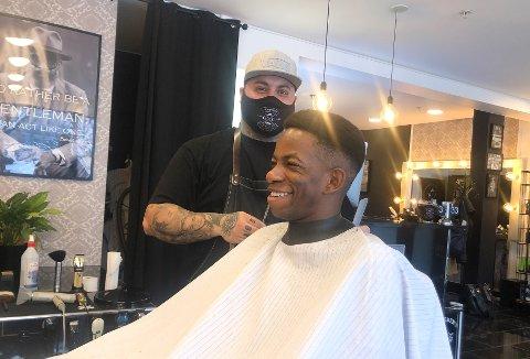 GENTLEMEN: Nima Jaffarione på Gentlemen's corner tar hånd om hårspissene til Mushaga Bakenga. Odd-spissen har nå fått tilbud om å forlenge oppholdet i Skien. Foto: Kristian Holtan