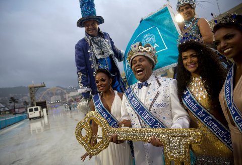 Carnival King Momo Wilson Neto, center holds the key to the city at a ceremony marking the official start of Carnival at the Sambadrome, in Rio de Janeiro, Brazil, Friday, March 1, 2019. Marcelo Crivella, mayor of Rio de Janeiro, opted not to attend the ceremony, and in his place Rio's Tourism President Marcelo Alves handed over the key. (AP Photo/Silvia Izquierdo)