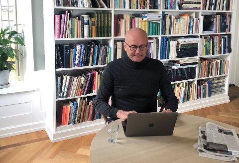 Festspill-direktør Anders Beyer foran bokhyllen i stuen sin hjemme i Danmark.