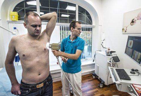 1 Benny Blomkvist stiller opp for å illustrere scanneren på Hudlegesenteret.  Vanligvis stiller pasienten kun i undertøy under fotograferingen.