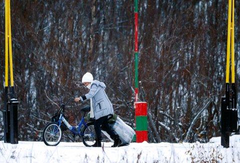 KIRKENES  20151116. En kvinne med sykkel og koffert passerer den norsk-russiske grensen på Storskog i Finnmark. Hun var blant  et tyvetalls asylsøkere som krysset grensen mandag formiddag. Foto: Cornelius Poppe / NTB scanpix