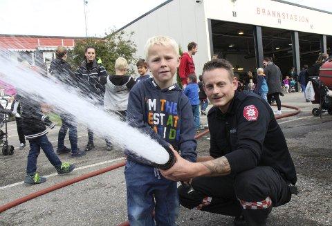 Gøy med vann: Alexander Tollander (t.v.) fikk prøve brannslangen under assistanse av Kristoffer Sveen. FOTO: kjell aasum  Kristoffer Sveen  Foto: Kjell Aasum  Brannstasjon åpen dag