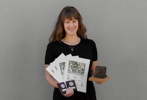 """VINNER: Fotograf Elisabeth Figenschou Jølstad ble i helgen kåret til """"Årets fotograf"""" av Vestfold fotograflaug. Her er hun avbildet med diplomer, medaljer og Daguerre-statuetten."""