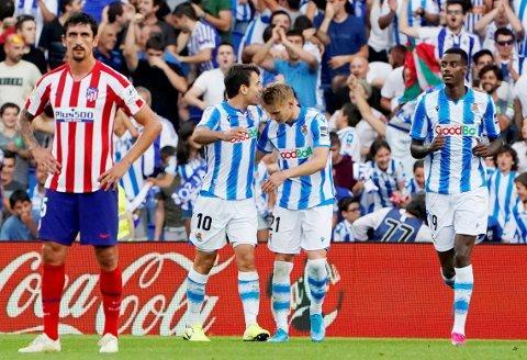 Martin Ødegaard ble den første til å score på den nyoppussede arenaen til Real Sociedad da han satte inn sitt andre mål for sesongen. Her jubler han med Mikel Oyarzabal. Alexander Isak til høyre. Atletico Madrids Stefan Savic (t.v.) er oppgitt. Atlético Madrid ble slått 2-0. Foto: VINCENT WEST / REUTERS / NTB scanpix
