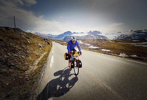 I ENSOMHET: Terje, sykkelen og fjella. Slik vil også mye av turen Canada på tvers arte seg for Terje Kolbjørnsen: Alene på en vei omgitt av høye fjell. Bildet er fra Jotunheimen Rundt tidlig i juli. FOTO: HÅKON MÆLAND, mlandpictures.com