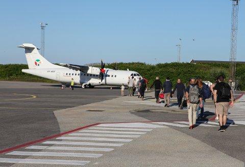 JUBILEUMSFLYET: Her går passasjerande inn i flyet som på dagen tek av 50 år sidan det første ruteflyet frå Florø lufthamn. Den gongen var det Widerøe som opererte. Dette var også det første flyet Danish Air Transport (DAT) letta med frå Florø på ni år.