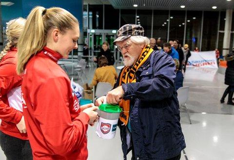 Per Steinar Lund var en av mange HTH-tilskuere som bidro med penger til Halden HKs bøssebærere, her ved Pernille Wang Skaug.
