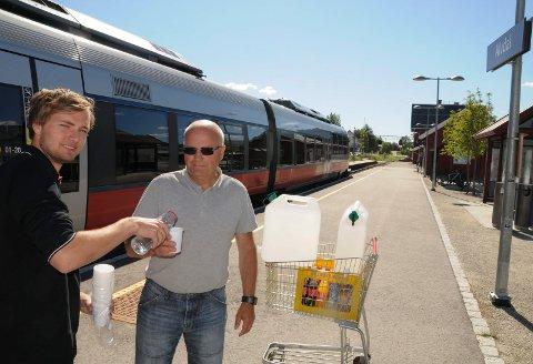 KOM MED DRIKKE: Jarle Sagbakken på Spar i Alvdal og Ivar Eggestad ordnet  med med vann og mineralvann til tørste,  iltre og overopphetede togpassasjerer på Rørosbanen forrige torsdag.