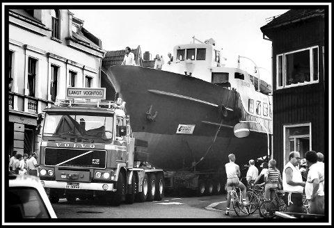 1986: Krabben fraktes gjennom Sarpsborg denne sommerkvelden. Fra Alvimkaia til Sarp kraftverk, der den ble heist ut i Glomma. Det gikk jo også i krabbefart denne dagen. På en Volvo F12. Båten har ikke fått på navnet Krabben ennå, så det står fortsatt Skjærhalden på siden. Altså båtens opprinnelige navn. Båten gikk på Glomma (og på grunn) fram til år 2000. I desember det året, gikk ferden tilbake til Alvimkaia, og ned til den andre byen igjen. Det gikk jo litt opp og ned med denne båten. Ikke bare på grunn av flere grunnstøtinger. Grunnlaget for økonomisk gevinst, var nok tuftet på et for tynt grunnlag. Så det var nok hovedgrunnen til at den havnet i Fredrikstad igjen.