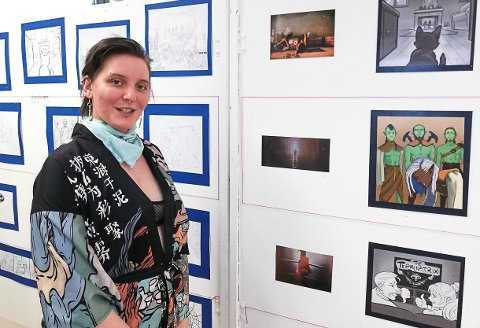 TEGNESERIER: Andrine Løvhøiden foran noen av sine tegneseriearbeider som utgjør hennes bacheloroppgave.