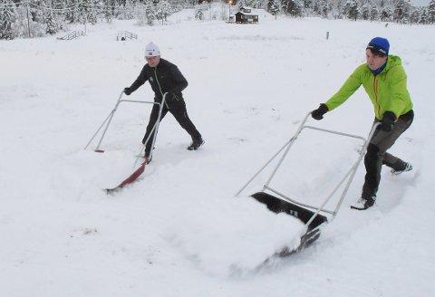 MÅKERDUGNAD: Per Jan Betten og Ole Sæterbø henter snø fra terrenget rundt og fyller på i traseen for å sikre gode forhold gjennom romjula og inn i det nye året.