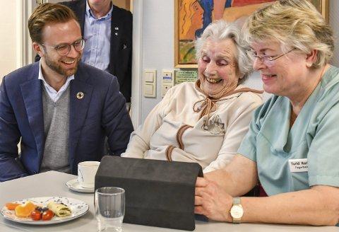 Prøver appen: Digitaliseringsminister Nikolai Astrup besøkte Strannasenteret for å høre om appen Appetitus. Her tester han ut applikasjonen sammen med bruker Astrid Solum (85) og fagarbeider Turid Harkjær.Foto: Mette Urdahl