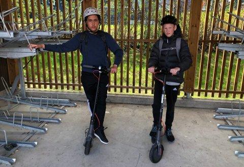 KJØRERELEKTRISK:Anthony Iversen (14, t.v.) og Magnus Lien (14) med forskriftsmessig hjelm og hver sin elsparkesykkel klare for hjemreisa opp den bratte Stasjonsveien.