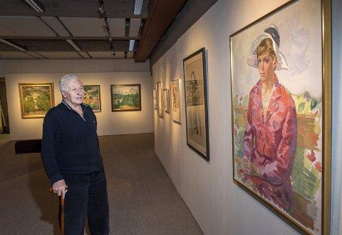 Birger Mowinckel stiller ut 122 av sine favorittbilder fra sin store malerisamling på Bryggen museum. Her med et maleri av sin kone Betty Eide Bull, malt av maleren Bjørn Tvedt. FOTO: EIRIK HAGESÆTER