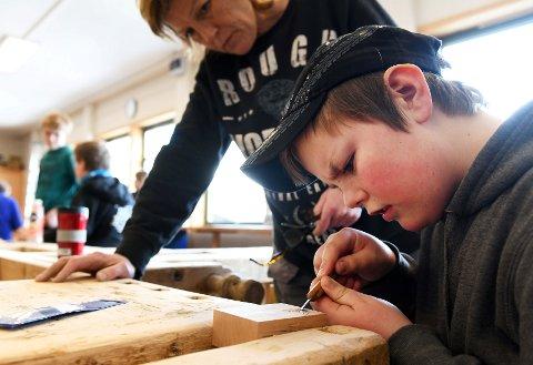 Øystein Bakke (13) i dyp konsentrasjon over treklossen med stjernemønster i sløydsalen på Vågå ungdomsskole. Bak følger treskjærer Kari Aasgaard med.