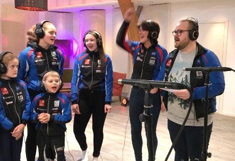 Berit Emma og Emil Markussen sammen med barn og unge fra Kjærstad IL i studio for å spille inn Kjærstad ILs nye klubbsang. Foto: Per Vikan