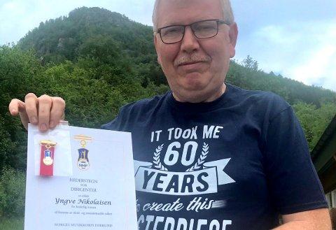 HEIDRA: Yngve Nikolaisen fekk i helga Noregs Musikkorpsforbund sitt heidersteikn. Dermed vanka det både diplom og medalje dagen etter 60-årsdagen hans. (Foto: Privat).