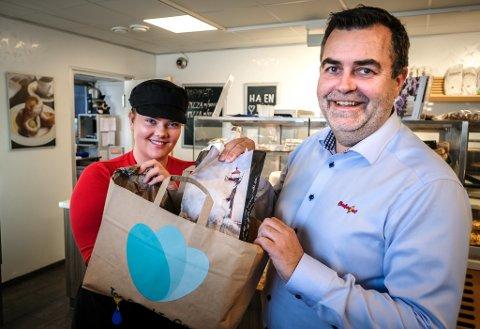 """Her viser Malin Fagerjord og Bjørn-Tore Hansen fram en pose med mat som er for god til å kastes. Med andre ord: """"Too Good To Go""""."""