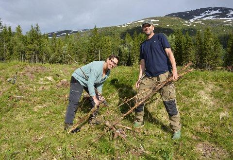 Dugnad: Anja og Marko Behsen fra Tyskland er i gang med å rydde området for småskog. Her står de ved en av grunnmurene til fangebrakkene. Foto: Karina Solheim
