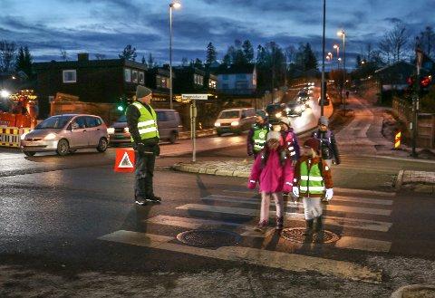 TRAFIKKFARLIG KRYSS: Per Rognerud hjelper barna som er på vei til Heggedal skole over Gjellumkrysset. - En gang telte jeg 44 biler osm kjørte på rødt lys i løpet av en time, forteller han.