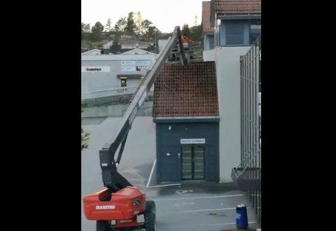 Her jobbar to personar frå ein lift med å spyle delar av taket på Fossbygget i Knarvik. Arbeidet skjedde både skjærtorsdag og langfredag i påska.
