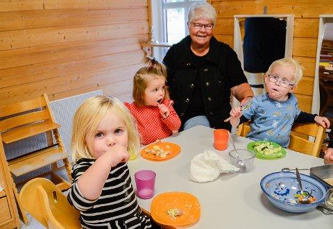 MATMOR: Hver torsdag trår Kari P. til i Prestfoss barnehage, hvor hun lager varm mat til barna. Fra venstre ser vi Eline Gjellum, Olivija Bacianskaite og Ole Grasvik som likte pølseformen som sto på menyen denne uken.