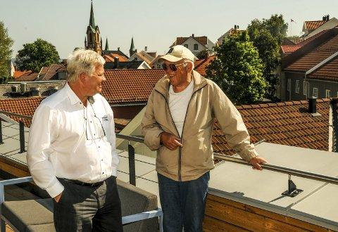 På bankens tak: Banksjef Jon Guste-Pedersen (t.v.) i en munter samtale med tegner og lokalhistoriker Carl Fredrik Monsen. De er begge strålende fornøyde med mottakelsen som heftet med tegninger av Kragerø i «gamle dager» har fått.