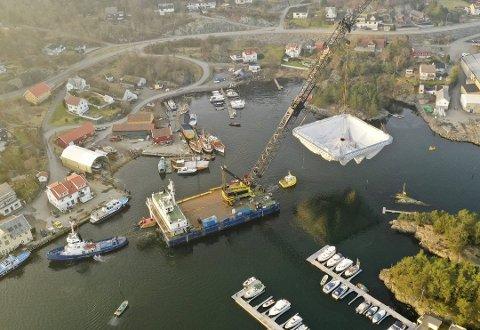 Tronds Marine Service er tildelt kontrakt i samband med bygginga av Hywind Tampen. Her løftar «Tronds Lift 6» ein ny type oppdrettsmerd ut av trongt farvatn i Sagvåg på Stord. Slepebåten «Eide Max» assisterer. Kunde var Ecomerden AS. Foto: Ecomerden AS