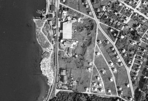 SKREDKANT: Utsnitt av flybilde av Rockwool-tomta med fabrikken Steinull A/S fra 1950, drøye to år før skredet i desember 1952. Fjordveien går på skrå opp mot venstre gjennom bildet. Kilde: norgeibilder.no/Kartverket.