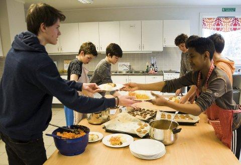 Marius Bolstad og Eyob Selmun i full gang med å lage til mat til medelevene.