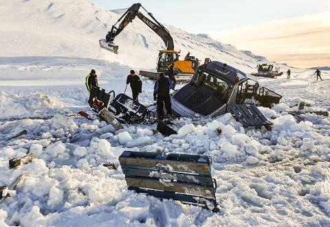 REDNINGSAKSJON: Løypemaskinen som gikk gjennom isen på Donkelitjern i Eggedal, ble søndag dratt opp av isvannet igjen ved hjelp av en beltegraver.