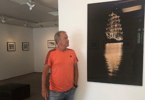 STENGT: Fjordgalleriet i Høyanger har stengt dørene. Her står galleridrivar og fotograf Arvid Fimreite ved eit av sine eigne fotografi som er utstilt i galleriet.
