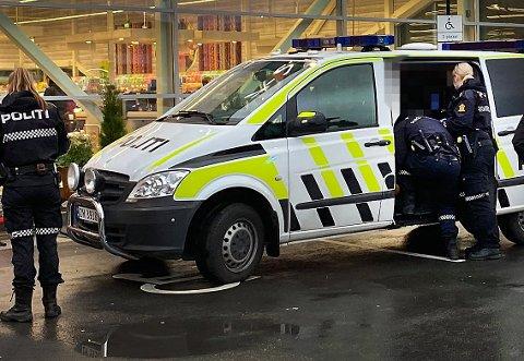 Her er butikktyven plassert i politibilen utenfor butikken. Foto: Marius Medby