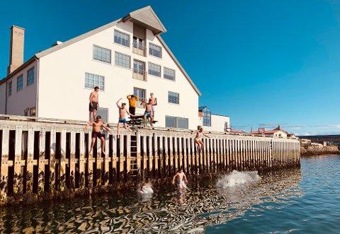 HOPPER I HAVET: Ungdommer er glade for å ha solen tilbake til byen, og hiver seg utfor bryggekanten i Vadsø.